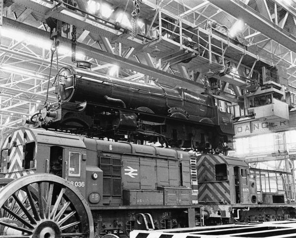 4-6-0 King class locomotive. Built 1927. Seen here at Swindon Works suspended above BR diesels No 08 036 and 08 675
