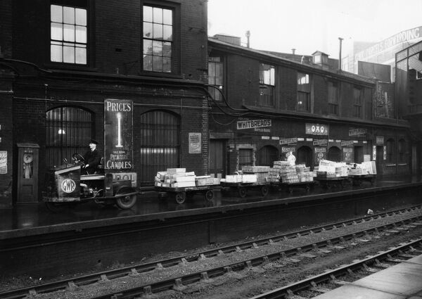 GWR tractor and trollies transporting parcels at the far end of Paddington Station. The GWR Parcels Fowarding Depot can be seen in the background