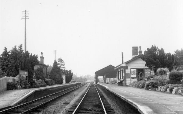 A deserted Adlestrop Station in July 1958. Photographed facing North towards Moreton-in-Marsh, the goods shed can be seen beyond the station building, and just behind that is the signal box