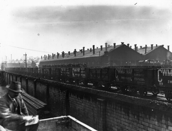 A view of the East Dock Engine shed at Cardiff with private owner wagons moving though the middle of the scene