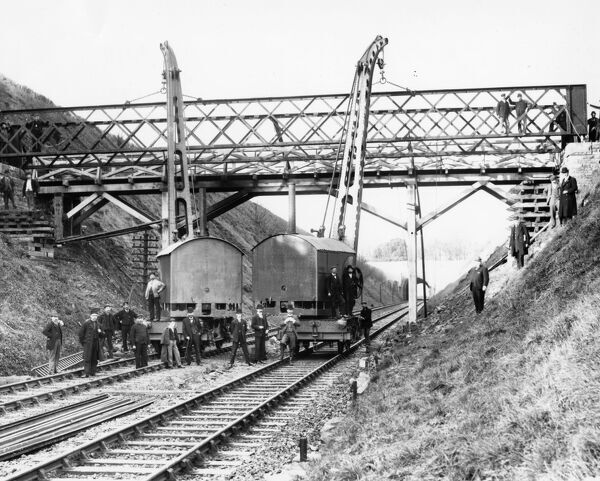 Two steam cranes lifting the girders of a footbridge into place
