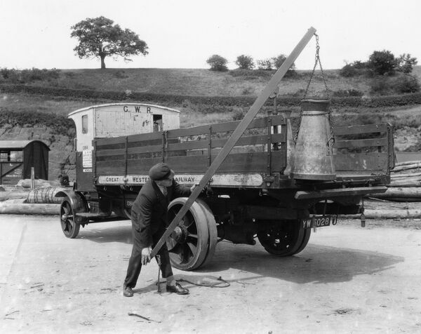 Seen here using lifting/lowering mechanism to lift milk churn from trailer