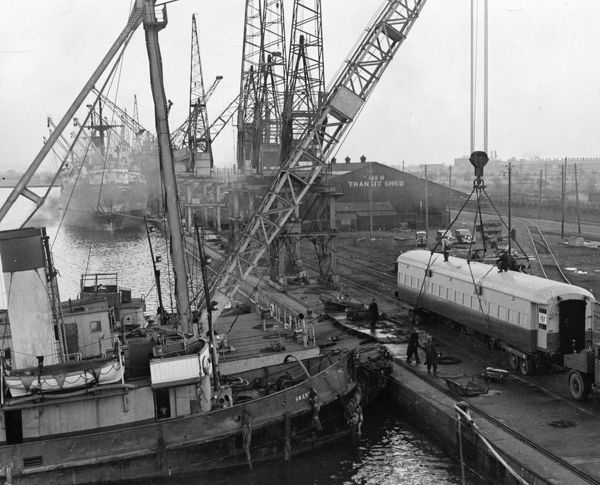 "50 ton floating crane lifting railway coach off road vehicle for shipment to Iraqi State Railway. Steam tug ""Swansea"" can be seen in the foreground"
