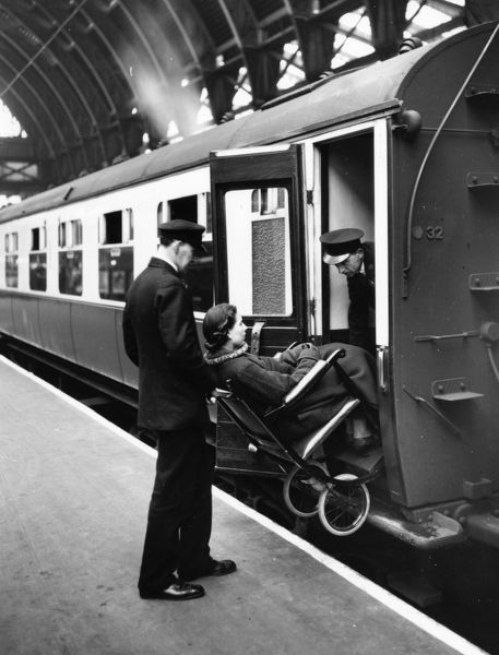 Paddington Station staff assisting a disabled passenger on to a carriage in 1937