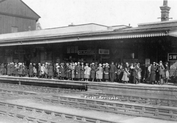 "The images is marked ""First Arrivals"" suggesting the passengers are awaiting a special train for a specific occasion"