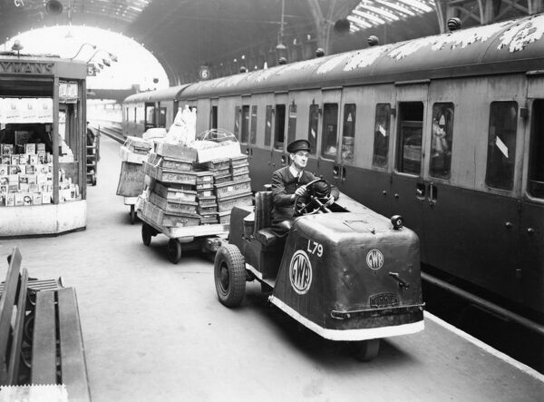 Three wheeled 'mechanical horse' driven by a GWR porter helps with the movement of parcels on Platform 5 at Paddington Station