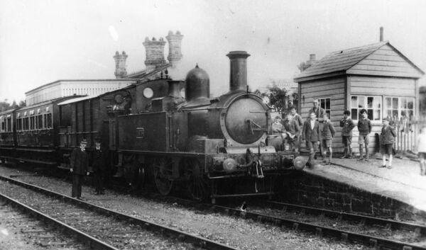 Tank engine no.1475 sits in the station with a crowd of young boys looking