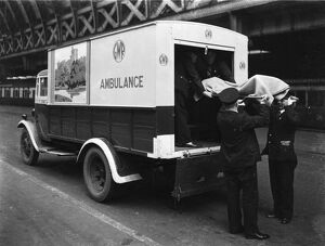 GWR staff loading a stretcher into a parcel van which has been converted into an ambulance