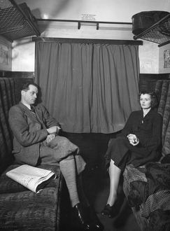 Publicity shot of couple in carriage, 1930s