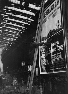 Woman pasting a billboard poster at Paddington station, 1943